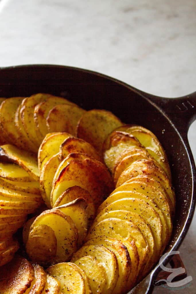 Crispy cooked Potatoes arranged in a spiral in a cast iron skillet